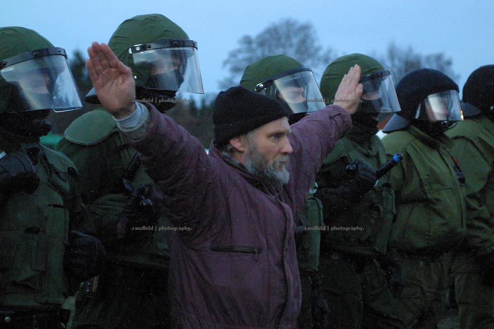 Ein Mann steht vor einer Reihe vermummter Polizisten und streckte die Arme aus, um die Gewaltfreiheit des Castorwiderstands zu symbolisieren.