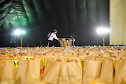 A volunteer takes a cart of food to hand out during a food drive for veterans at the Bridgeview Sports Dome. November 21st, 2015, in Bridgeview. (Gary Middendorf-Daily Southtown)