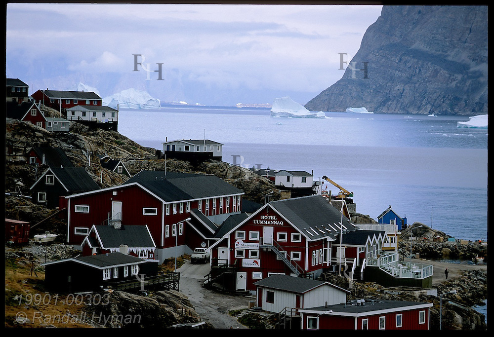 Colorful, Danish-style wooden homes cling to rocky slopes overlooking icebergs and fjord at island town of Uummannaq, Greenland