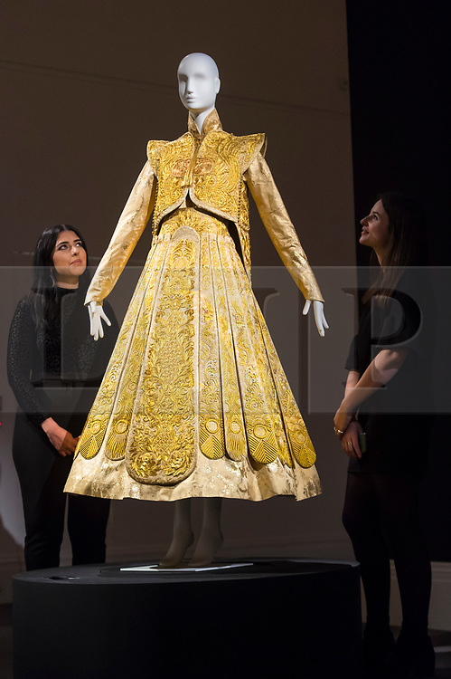 "© Licensed to London News Pictures. 25/10/2019. LONDON, UK. Staff members pose with a ""Gold Chinese traditional bridal dress"" by Guo Pei (Est.  GBP500-700k).  Preview of ""GOLD: The Midas Touch"" at Sotheby's in New Bond Street.  Artworks spanning six centuries dedicated to gold will be offered for sale on 29 October.  Photo credit: Stephen Chung/LNP"