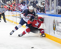 MAGNITOGORSK, RUSSIA - APRIL 20: USA's Ty Emberson #10 bodychecks Switzerland's Jesse Tanner #17 during preliminary round action at the 2018 IIHF Ice Hockey U18 World Championship. (Photo by Steve Kingsman/HHOF-IIHF Images)