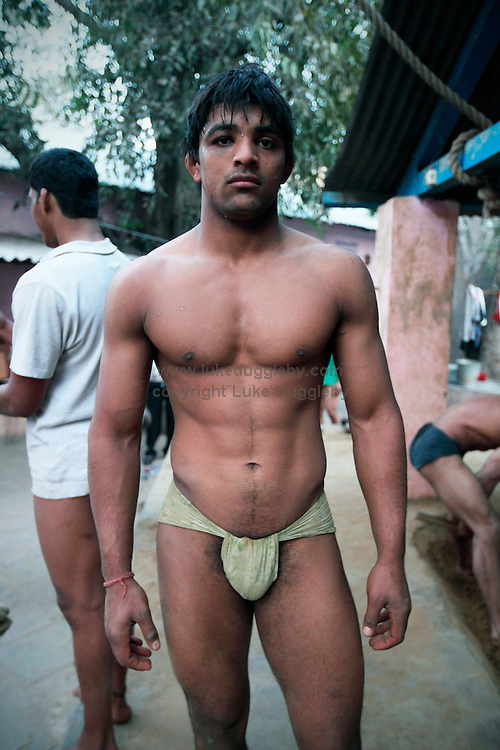 An Indian wreslter at the Hauman Akhara. For almost 3000 years loincloth clad duels on mud have transfixed spectators across India. Yet wrestling in India is a sport in transition. In 2004 the Indian Fighters Federation tried to prohibit the practice of traditional mud wrestling, claiming that for India to compete at an international level fighters must train using mats. Whilst competing on mud can earn good money for a wrestler at events called dungals in India's countryside, the techniques are starkly different. .The Guru Hanuman Akhara, a wrestling school in Old Delhi, is the epicentre of this ancient wrestling tradition as it begins to enter the modern world. Now training fighters on both mats and mud the school has produced hundreds of champions at both domestic and international level..Established in 1925, making it the oldest in India, it was in 1955 that Vijay Pal, or Guru Hanuman as he later became known, took over the coaching..Born to a poor family in the desert state of Rajasthan he chose never to marry and instead dedicated his whole life to wrestling, becoming a legend, who created a model for modern Indian wrestling by combining traditional Indian wrestling called Kushti with international standards. His statue and mausoleum stands overlooking the outer courtyard of the school.....