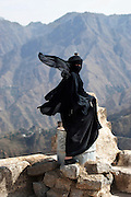 """Black Angel"" by Amira Al Sharif. Twenty year old Amal Ahmed stands in Hajah castle (Hajah, Yemen).  She is a mother of three children. She got married when she was fifteen years old and has three kids.  She studies from home despite all the obstacles she faces."