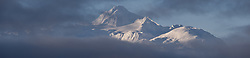 DIGITAL COMPOSITE PANORAMA (multiple overlapping images stitched together): Four Winds Mountain near Haines, Alaska and near the border with Alaska and British Columbia, Canada rises out of low-lying clouds. This view of the mountain is from the Alaska Chilkat Bald Eagle Preserve.