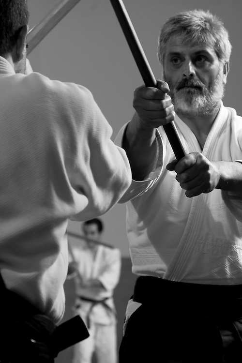 During an aikido seminar, two practicioners engage in weapons practice with wooden swords, or bokken.