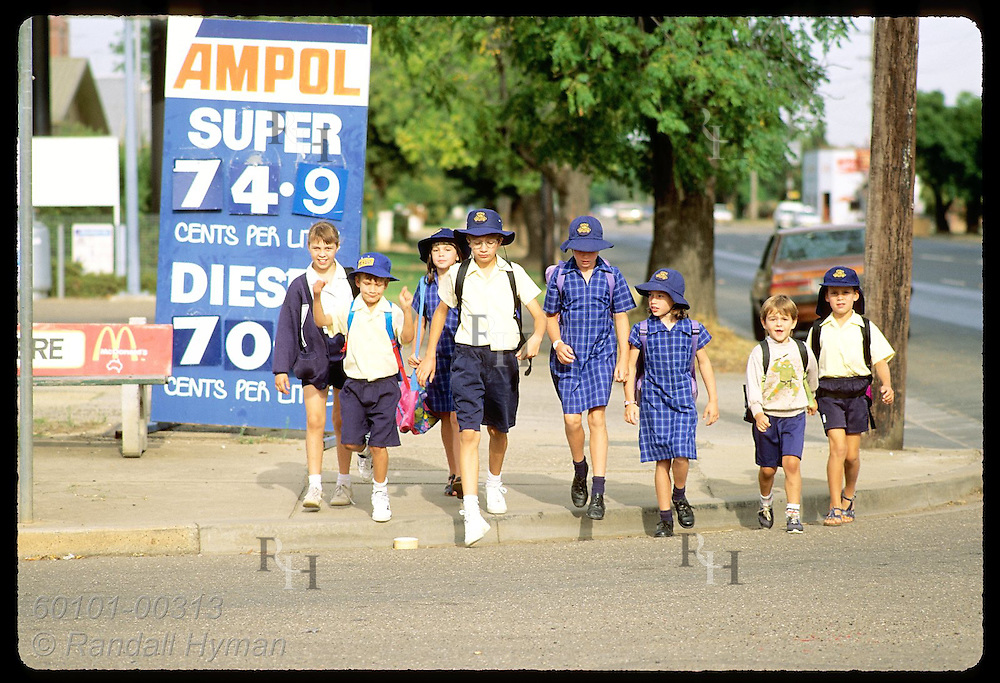 Girls and boys in uniforms walk to school together past petrol station sign in Wagga Wagga, NSW Australia
