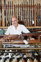 Portrait of happy mature owner of gun shop