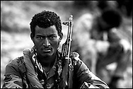 An Eritrean soldier crouches in a trench at the front lines of Tsorona, approximately 60kms south of the capital Asmara, in scenes reminiscent of the First World War. Up to half a million soldiers from both sides face each other along the 1000 km border. Eritrea has been embroiled in a bitter 22 month border war with neighbouring Ethiopia in which over 50,000 soldiers have died. .