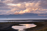 A storm clouds part at sunset over Beluga Slough on the Kachemak Bay in Homer, Alaska.