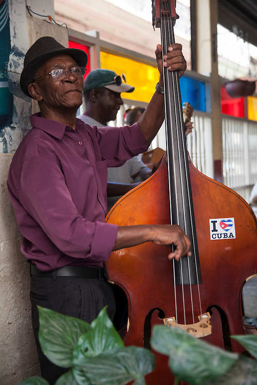 A double bass player belonging to a salsa music band performs at a local cafe in Old Havana, Cuba.