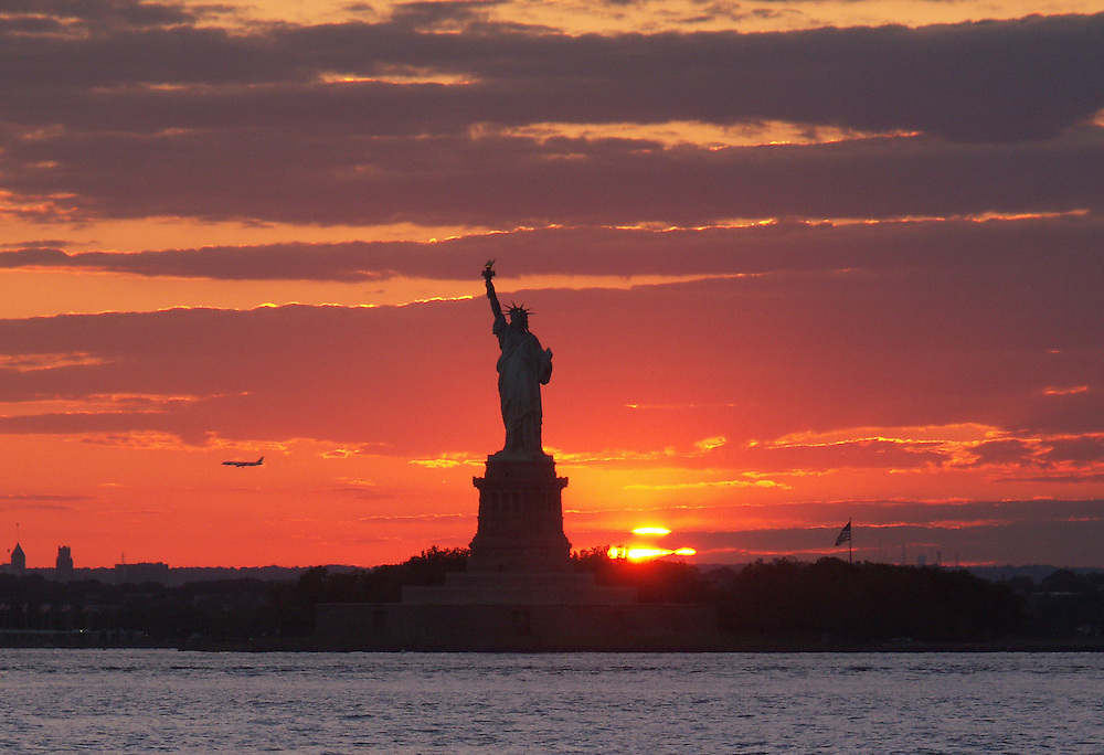 The sun sinks below the horizon next to Lady Liberty on June 3, 2004.