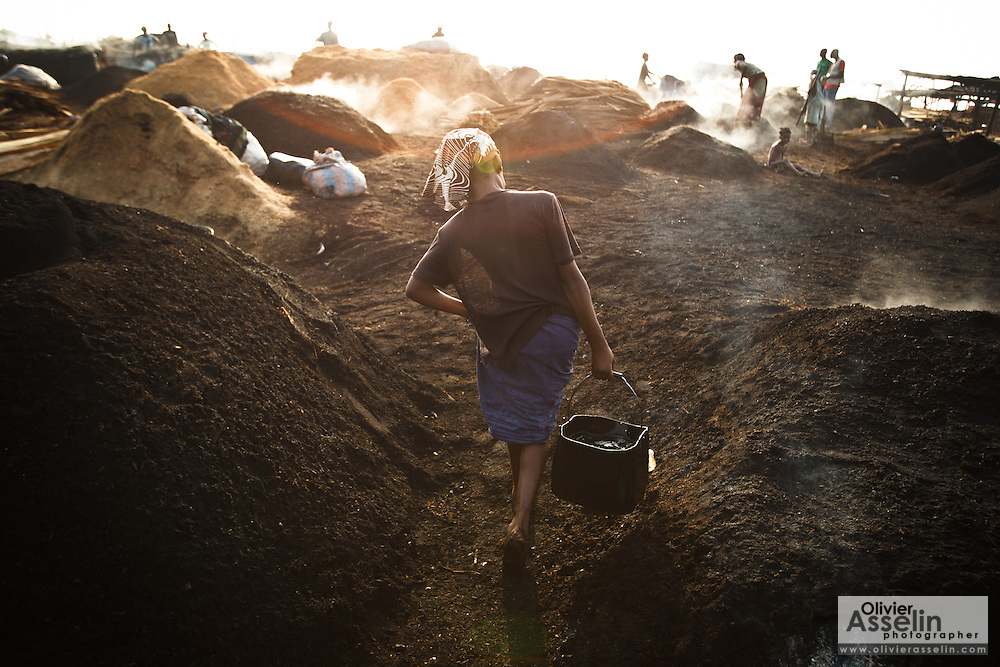 A carries a bucket of water she will use to cool off charcoal at a wood charcoal production site on the outskirts of San Pedro, Bas-Sassandra region, Côte d'Ivoire on Sunday March 4, 2012. Men, women and children - who don't go to school - work here seven days a week.