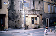 Boy in courtyard square Mende Lozere southern France with old closed down local traditional French shop 1987