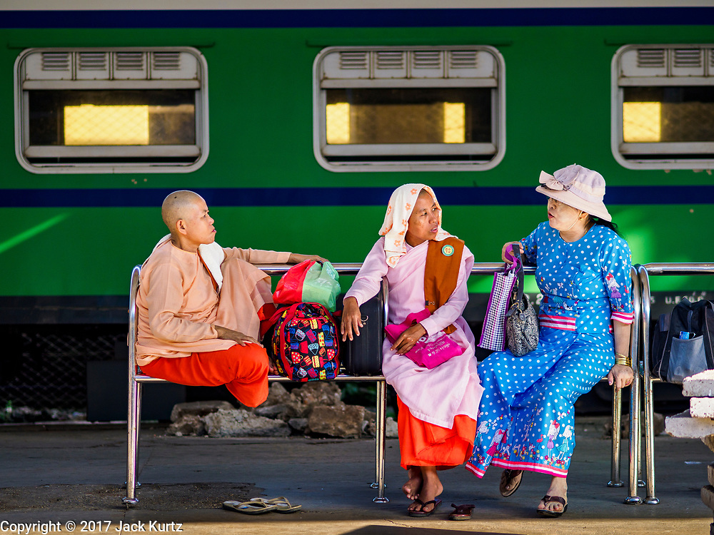25 NOVEMBER 2017 - YANGON, MYANMAR: Women wait for a train in the Yangon Central Railroad Station. The Yangon Circular Train is a 45.9-kilometre (28.5 mi) 39-station two track loop system connects satellite towns and suburban areas to downtown. The train was built during the British colonial period, the second track was built in 1954. Trains currently run both directions (clockwise and counter-clockwise) around the city. The trains are the least expensive way to get across Yangon and they are very popular with Yangon's working class. About 100,000 people ride the train every day. A a ticket costs 200 Kyat (about .17¢ US) for the entire 28.5 mile loop.    PHOTO BY JACK KURTZ