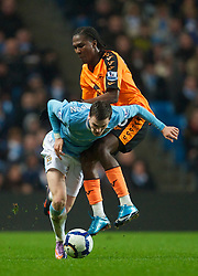 WIGAN, ENGLAND - Monday, March 29, 2010: Manchester City's Adam Johnson and Wigan Athletic's Hugo Rodallega during the Premiership match at the City of Manchester Stadium. (Photo by David Rawcliffe/Propaganda)