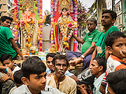 "22 OCTOBER 2015 - YANGON, MYANMAR: Hindus in Yangon participate in a Navratri procession to the Sri Kali Temple. Navratri, literally ""nine nights"" is a Hindu festival devoted to the Goddess Durga. Navratri festival combines ritualistic puja (prayer) and fasting. Navratri in India follows the lunar calendar and is celebrated in September/October as Sharad Navratri. It's widely celebrated in countries in Southeast Asia that have large Hindu communities, including Myanmar (Burma). Many of Myanmar's Hindus are descendants of Indian civil servants and laborers who came to Myanmar when it was the British colony of Burma.   PHOTO BY JACK KURTZ"