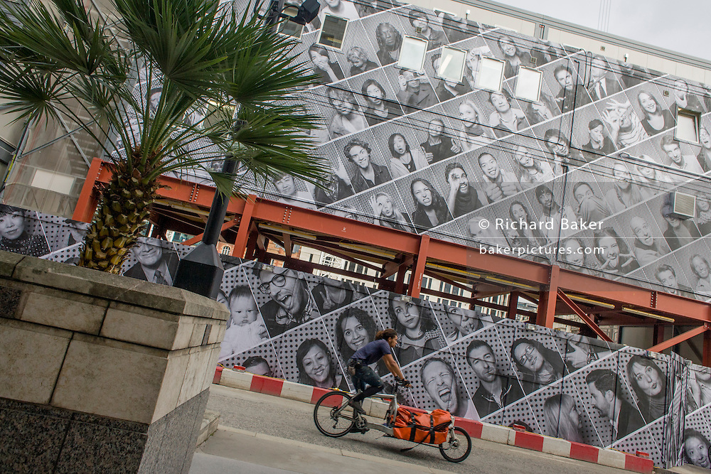 Delivery cyclist pedals past a site office and a construction hoarding featuring dozens of London faces in the City.