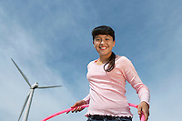 Girl (7-9) holding hula hoop at wind farm, portrait