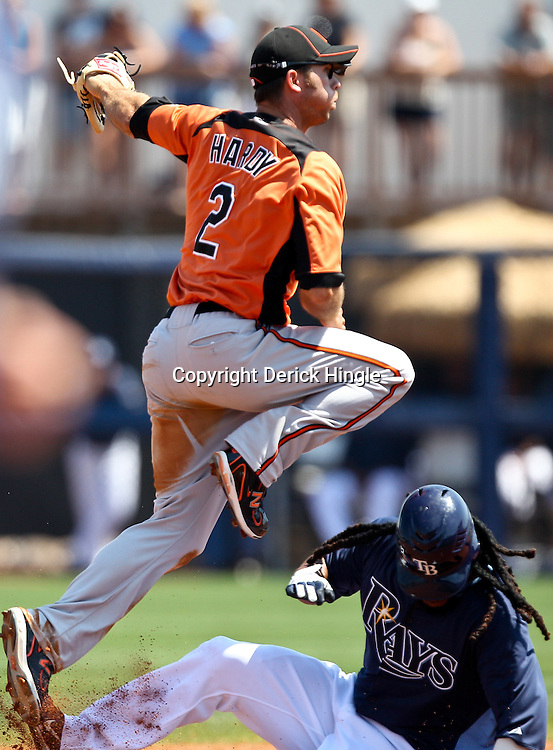 March 20, 2011; Port Charlotte, FL, USA; Baltimore Orioles shortstop J.J. Hardy (2) leaps over Tampa Bay Rays left fielder Manny Ramirez (24) after getting a force out at second base during a spring training exhibition game at Charlotte Sports Park.   Mandatory Credit: Derick E. Hingle