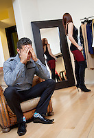 Worried young man sitting on armchair with woman in background trying on clothes