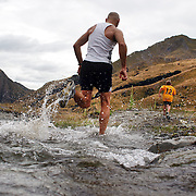 Runners cross Moke Creek on the Ben Lomond High Country Station during the Pure South Shotover Moonlight Mountain Marathon and trail runs. Moke Lake, Queenstown, New Zealand. 4th February 2012. Photo Tim Clayton