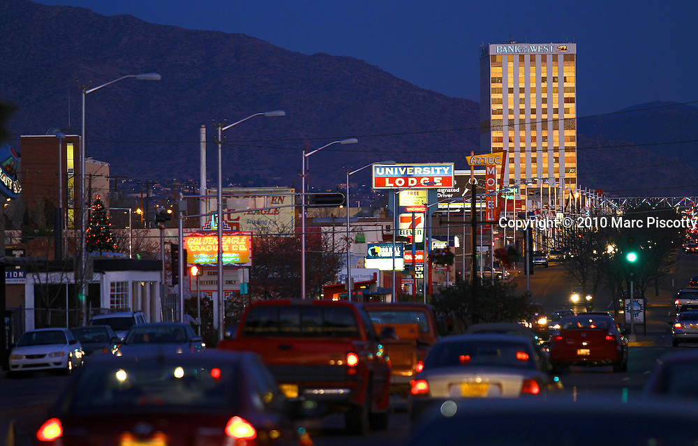 SHOT 12/28/10 6:19:35 PM - Traffic along Central Avenue in Albuquerque, N.M. as the sun starts to set one evening. Central Avenue is a major east-west street in Albuquerque, New Mexico, which historically served as the city's main thoroughfare and principal axis of development. It runs through many of Albuquerque's oldest neighborhoods, including Downtown, Old Town, Nob Hill, and the University of New Mexico area. Central Avenue was part of U.S. Route 66 from 1937 until the highway's decommissioning in 1985 and also forms one axis of Albuquerque's house numbering system. Albuquerque is the largest city in the state of New Mexico. It is the county seat of Bernalillo County and is situated in the central part of the state, straddling the Rio Grande. in 2009 the city's population was 528,497 according to U.S. census estimates which ranks it as the 34th-largest city in the U.S. As of June 2007, the city was the sixth fastest-growing in America. The Sandia Mountains run along the eastern side of Albuquerque, and the Rio Grande flows through the city, north to south..(Photo by Marc Piscotty / © 2010)