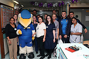 Haydon the Womble, AFC Wimbledon defender Will Nightingale (5), AFC Wimbledon attacker Egli Kaja (21), AFC Wimbledon midfielder Anthony Hartigan (8), AFC Wimbledon first team coach Glyn Hodges, AFC Wimbledon defender Rod McDonald (26) delivering Christmas presents to the children on behalf of AFC Wimbledon, at St George's Hospital, Tooting, United Kingdom on 13 December 2018.