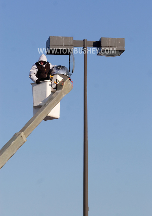 Middletown, New York - A worker in a bucket truck replaces a light in a parking lot in a shopping plaza on Feb. 6, 2007.