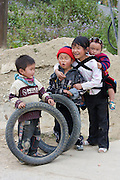 On the road from Pa Tan to Sinho. Hilltribe kids playing with motorcycle tyres.