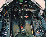 A detailed view of a Mark 1 Hawk jet belonging to 'Synchro Leader' of the elite 'Red Arrows', Britain's prestigious Royal Air Force aerobatic team. We see the flight controls and instrument panels looking grubby and worn with grey paint rubbed or flaking off. This version of the BAE Systems Hawk is low-tech without computers nor fly-by-wire technology it is one of the most user-friendly modern jets to fly and serves as a first step trainer for pilots to accumulate fast-jet flying hours and who are destined for the most sophisticated of fast military fighters in the future. Their aerobatic displays demands that their workhorse machine must have phenominal turning circle ability and rate of climb. The team's aircraft are in some cases over 25 years old and their airframes require constant attention, with frequent engineering overhauls needed. .