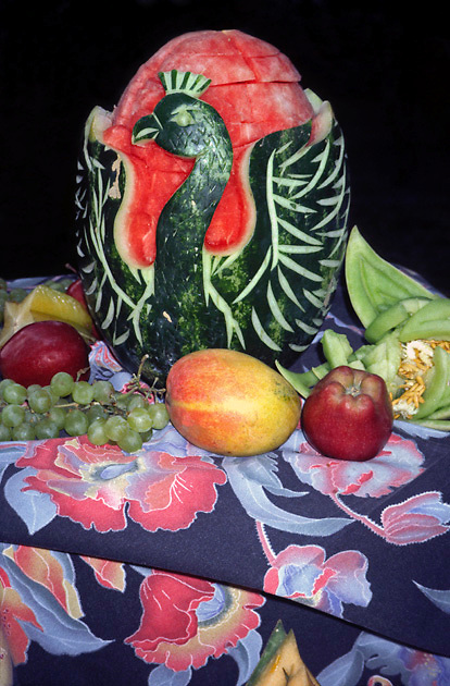 carved watermelon swan-shape; apples; grapes; honeydew melon; mango; starfruit; floral tablecloth; centerpiece; tasty; nutritious food; appetizing decoration