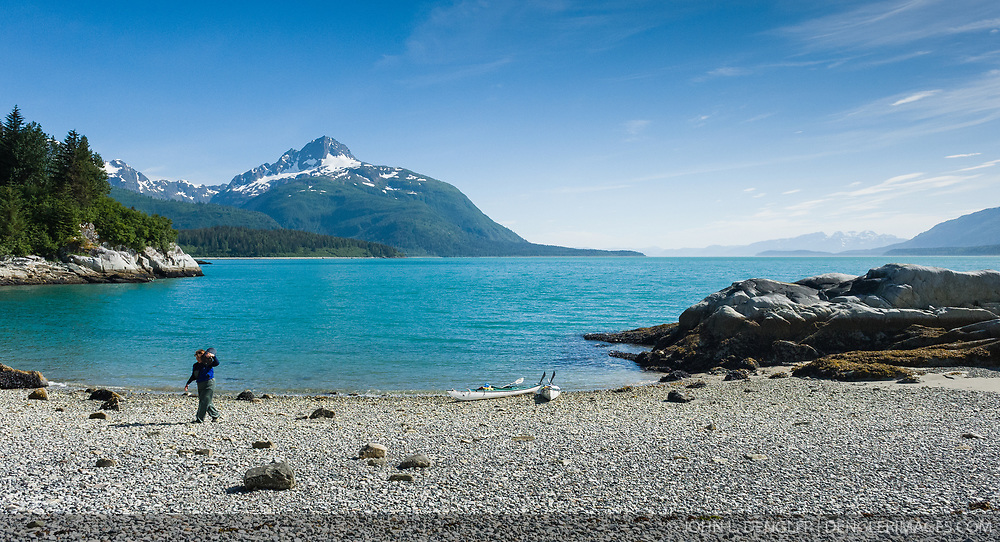 A kayaker stashes their bear resistant food container after landing on a beach near the Klotz Hills and not far from Maquinna Cove in Muir Inlet in Glacier Bay National Park and Preserve in southeast Alaska. Prominent in the background is Mt. Wright which is located at the mouth of Adams Inlet. Use of a bear resistant food container is required by the park as a way to control conflicts with black and grizzly bears.