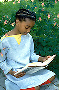 Young studious girl age 9 reading in her backyard garden.  St Paul  Minnesota USA