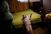 "Gabby, 2, plays on the bed she shares with her mother, Lettorea ""Lottie"" Clark, 25, in Albany, GA on Wednesday, October 22, 2008 while her mother cleans the room. Lottie and Gabby live off welfare after escaping an abusive relationship with Gabby's father."