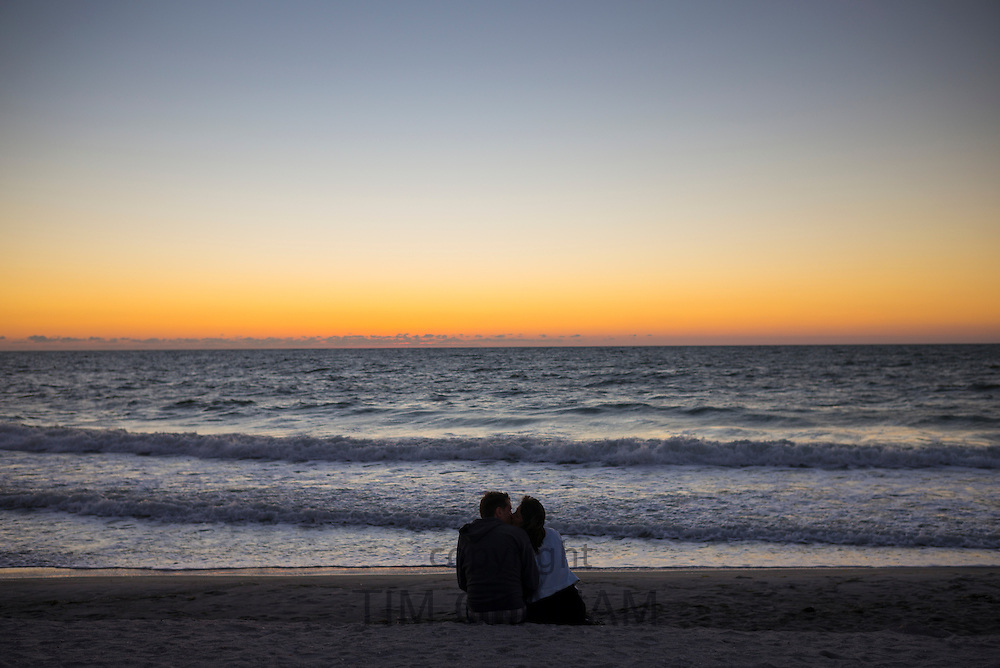 Romantic young couple watching the sunset on Captiva Island in Florida, USA