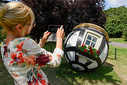 "© Licensed to London News Pictures. 03/07/2019. LONDON, UK. A woman photographs ""Tudor Ball"", 2019, by Lars Fisk. Frieze Sculpture opens in Regent's Park, London's largest free display of outdoor art.  Works from 23 international artists are on display 3 July to 6 October 2019.  Photo credit: Stephen Chung/LNP"