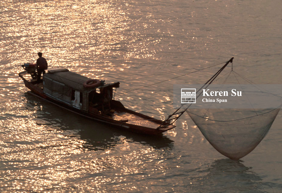 Fishing boat along the Three Gorges of the Yangtze River at sunset, China