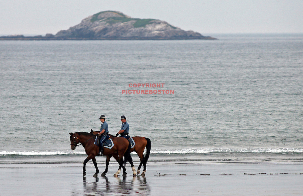 "(06/22/08-Nahant,MA) State Troopers on horseback patrol Nahant Beach with ""Egg"" Rock in the background.."