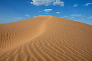 Sahara desert sand dune with cloudy blue sky at Erg Lihoudi, M'hamid, Morocco