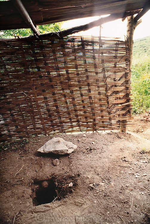 Namgay family toilet in Shingkhey, Bhutan, was part of a program mandated by the country's king to force the Bhutanese to use a specific location for toileting. This program has not been a success. Most families still use the surrounding bushes and fields (1994). Shingkhey Village, Bhutan. From Peter Menzel's Material World Project.