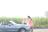 Women reading map on convertible at countryside