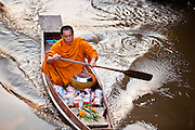 "10 JULY 2011 - AMPHAWA, SAMUT SONGKRAM, THAILAND:   A Buddhist monk from Wat Amphawan Chetiyaram in Amphawa, Thailand, about 90 minutes south of Bangkok, approaches a home on the main canal during his alms round. Most of the monks from the temple use boats to go from house to house on their alms rounds. The Thai countryside south of Bangkok is crisscrossed with canals, some large enough to accommodate small commercial boats and small barges, some barely large enough for a small canoe. People who live near the canals use them for everything from domestic water to transportation and fishing. Some, like the canals in Amphawa and nearby Damnoensaduak (also spelled Damnoen Saduak) are also relatively famous for their ""floating markets"" where vendors set up their canoes and boats as floating shops.      PHOTO BY JACK KURTZ   PHOTO BY JACK KURTZ"