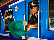 11 APRIL 2018 - BANGKOK, THAILAND: An engineer waves a green flag as his train leaves Hua Lamphong train station in Bangkok on the first day of the Songkran travel period. Songkran is the traditional Thai New Year and is one of the busiest travel periods of the year as Thais leave the capital and go back to their home provinces or resorts in tourist areas. Trains and busses are typically jammed the day before the three day Songkran holiday starts. The government has extended the official holiday period through Monday, 16 April because one day of the Songkran holiday fell on the weekend, giving many workers a five day holiday.      PHOTO BY JACK KURTZ