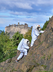 Pictured: Joy Maria Onotu and Sarah Miele on the crags with Edinburgh Castle in the background.<br /> <br /> Stars of the Fringe show 'Valentina's Galaxy' appeared as astronauts on iconic Salisbury Crags in Edinburgh in preparation for their show at this year's Edinburgh Fringe.<br /> <br /> © Dave Johnston / EEm