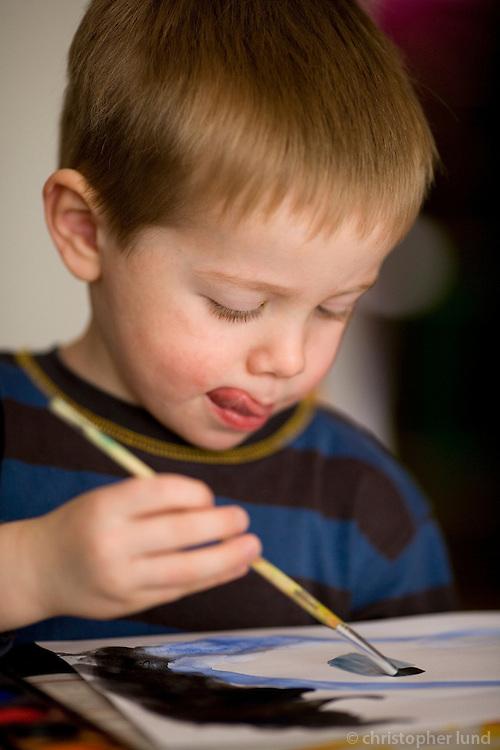 Young boy painting with watercolors at home. Ari Carl að vatnslita við stofuborðið heima.