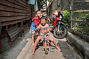"Mar. 21, 2009 -- BANGKOK, THAILAND:  Children play in an alley in the Monk's Bowl Village. The Monk's Bowl Village on Soi Ban Baat in Bangkok is the only surviving one of what were originally three artisan's communities established by Thai King Rama I for the purpose of handcrafting ""baat"" the ceremonial bowls used by monks as they collect their morning alms. Most monks now use cheaper factory made bowls and the old tradition is dying out. Only six or seven families on Soi Ban Baat still make the bowls by hand. Most of the bowls are now sold to tourists who find their way to hidden alleys in old Bangkok. The small family workshops are only a part of the ""Monk's Bowl Village."" It is also a thriving residential community of narrow alleyways and sidewalks.     Photo by Jack Kurtz"