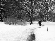 Couple walking on a snowy path on Cherry Hill toward Bethesda Terrace in Central Park.