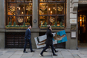 An employee from an insurance company walks through the City of London, visiting specific addresses relevant to the man appearing in a beach portrait whose 50th birthday it is, part of a creative and fun idea for the company's Christmas party, on 14th December 2017, in the City of London, England.