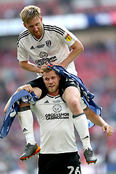 Fulham's Tim Ream (top) and Tomas Kalas celebrate promotion after the final whistle during the Sky Bet Championship Final at Wembley Stadium