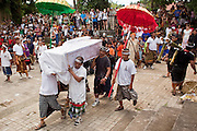 Apr. 25 -- UBUD, BALI, INDONESIA:  Members of the family carry the coffin of Cokorde Gede Raka around the cremation site. Cokorde, a member of Ubud's royal family, was cremated Sunday, Apr. 25. Balinese are Hindus and cremate their dead. Balinese funerals are elaborate - and expensive - affairs. A funeral for one person costs a minimum of 45 million rupiah (about $5,000 US). The body is placed into the bull's body at the cremation and cremated in the bull. The funeral pyre is burnt adjacent to the bull. That is what a family may earn in two to three years. The result is that only the rich can afford formal cremations. The body (in the casket) is placed in the top of the funeral pyre and the procession takes the body to the cremation site. The funeral pyre, and the body, are spun at intersections to confuse the spirits so the soul doesn't try to return to its home and to confuse evil spirits.    PHOTO BY JACK KURTZ